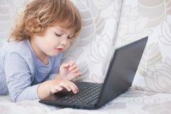 Portret del primo piano di poca ragazza dei capelli del ricciolo che lavora al computer portatile Immagine Stock Libera da Diritti