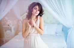 Portret delikatny zmysłowy dziewczyny brunetki obsiadanie na białym b obrazy stock