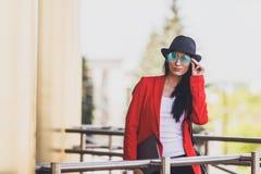 Portret della giovane donna felice dei pantaloni a vita bassa con il rivestimento black hat e rosso d'uso degli occhiali da sole  Immagini Stock Libere da Diritti