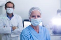 Portret dentysta i stomatologiczny asystent jest ubranym chirurgicznie maskę obraz stock