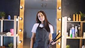 Portret des lächelnden Schönheitsfriseurs mit dem schwarzen Schutzblech, das Kamera beim Halten des Berufsfriseurs betrachtet stock footage