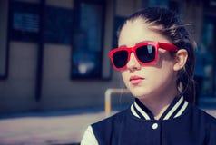 Portret dichte omhooggaand van een modieus meisje in rode zonnebril Royalty-vrije Stock Foto
