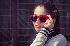 Portret dichte omhooggaand van een modieus meisje in rode zonnebril Royalty-vrije Stock Fotografie