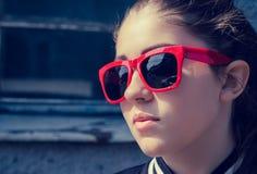 Portret dichte omhooggaand van een modieus meisje in rode zonnebril Royalty-vrije Stock Foto's