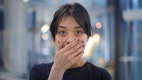 Portret dichte omhooggaand van emotioneel Aziatisch meisje die haar tong tonen stock footage