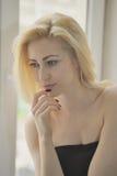 Portret dichte omhooggaand van jonge mooie blondevrouw dichtbij venster stock fotografie
