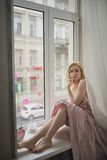 Portret dichte omhooggaand van jonge mooie blondevrouw dichtbij venster royalty-vrije stock foto's