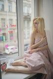 Portret dichte omhooggaand van jonge mooie blondevrouw dichtbij venster stock foto