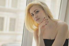 Portret dichte omhooggaand van jonge mooie blondevrouw dichtbij venster royalty-vrije stock afbeeldingen