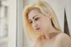 Portret dichte omhooggaand van jonge mooie blondevrouw dichtbij venster stock foto's