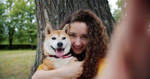 Portret die van aantrekkelijke dame selfie met puppy in park nemen die koesterend hond kussen stock video