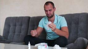 Portret die van aantrekkelijke kerel met een neusnevel en weefsel in handen, neus het gebruiken daalt, concept behandeling voor a stock footage