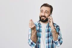 Portret die van aantrekkelijke kerel die, via smartphone over dolkomisch iets spreken, tonend Italiaans gebaar, over lachen royalty-vrije stock foto