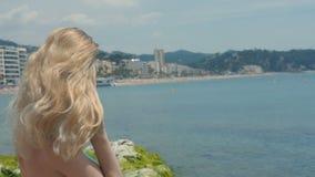 Portret die van aantrekkelijke vrouw zich bij strand bevinden Gelukkig glimlachend meisje die camera bij kust bekijken Jonge blon stock videobeelden