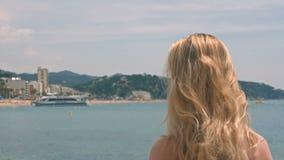 Portret die van aantrekkelijke vrouw zich bij strand bevinden Gelukkig glimlachend meisje die camera bij kust bekijken Jonge blon stock footage