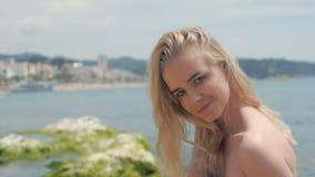Portret die van aantrekkelijke vrouw zich bij strand bevinden Gelukkig glimlachend meisje die camera bij kust bekijken Jonge blon stock video