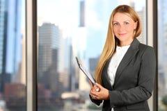 Portret die van bedrijfsvrouw zich dichtbij venster bevinden stock foto