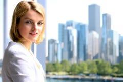 Portret die van bedrijfsvrouw zich dichtbij venster bevinden Het gebieds van de binnenstad achtergrond royalty-vrije stock afbeelding