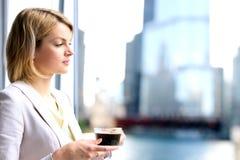 Portret die van bedrijfsvrouw zich met koffie dichtbij venster bevinden stock afbeeldingen