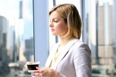 Portret die van bedrijfsvrouw zich met koffie dichtbij venster bevinden Het gebieds van de binnenstad achtergrond royalty-vrije stock foto