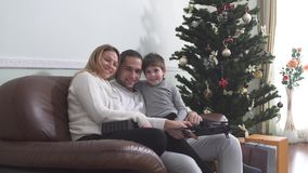 Portret die van blije familie zitting met hommel op een leerstoel omhelzen dichtbij de Kerstmisboom Gelukkig familieconcept stock video