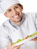 Portret die van chef-kokkok saladeschotel aanbieden Royalty-vrije Stock Afbeeldingen