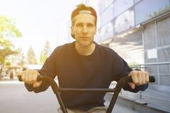 Portret die van de cheereful jonge mens op de fiets, in de stadsstraten berijden royalty-vrije stock foto's