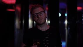 Portret die van de droevige mens zich met dicht omhoog glas van alcohol bij de disco bevinden Mens die in glazen camera bekijken, stock footage