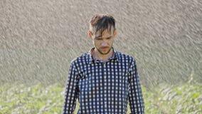 Portret die van de droevige mens zich onder de regen bevinden stock video