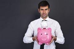 Portret die van de jonge mens een spaarvarken twee houden Stock Afbeelding