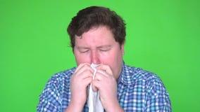 Portret die van de jonge mens in plaidoverhemd met allergie of koude, zijn neus met een weefsel het blazen, isoleerde het groene  stock video
