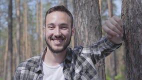 Portret die van de knappe jonge mens in het pijnboombos, in het camera en het glimlachen close-up kijken Eenheid met wilde aard stock video
