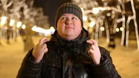 Portret die van de knappe mens een wens maken in openlucht tijdens koude de winternacht stock video