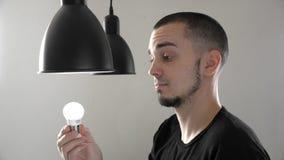 Portret die van de mens de oude gloeiende bol vervangen met een nieuwe energie efficiënte LEIDENE bol in lamp Het schroeven energ stock videobeelden