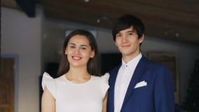 Portret die van de mooie jonge paarmens en vrouw in buitensporige kleding die zich in restaurant verenigen, camera bekijken stock video