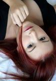 Portret die van de roodharige het jonge vrouw op het bed leggen Royalty-vrije Stock Fotografie