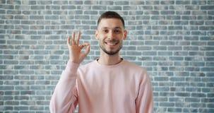 Portret die van de vrolijke mens O.K. gebaar tonen die op bakstenen muurachtergrond glimlachen stock videobeelden