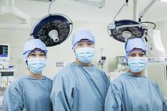 Portret die van drie chirurgen die op een rij chirurgische maskers in de werkende ruimte dragen, camera bekijken Stock Afbeeldingen