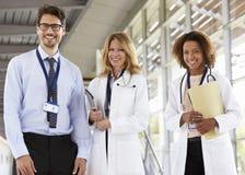 Portret die van drie mannelijke en vrouwelijke artsen, aan camera kijken royalty-vrije stock afbeelding