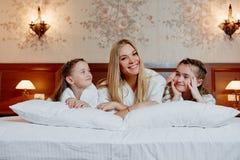 Portret die van een gelukkige moeder en haar kinderen op een bed liggen Stock Afbeelding