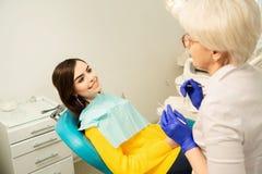 Portret die van een glimlachende vrouw, bij de tandstoel met arts op het tandkantoor zitten stock foto