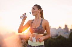 Portret die van een jonge aantrekkelijke vrouw in sportkleding, luisteren aan Stock Foto's