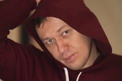 Portret die van een jonge mens in een kap, de camera, close-up bekijken royalty-vrije stock afbeelding