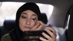 Portret die van een jonge moslimvrouw in zwarte headscarf, in de auto zitten terwijl het bekijken een kleine kosmetische spiegel  stock videobeelden