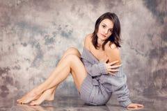 Portret die van een jonge vrouw in studio, op de vloer liggen Royalty-vrije Stock Fotografie