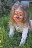 Portret die van een klein meisje met de make-up van tijgeraqua, en in een park glimlachen zitten Royalty-vrije Stock Afbeelding