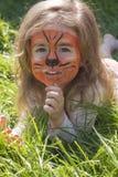 Portret die van een klein meisje met de make-up van tijgeraqua, op het groene gras liggen Stock Afbeelding