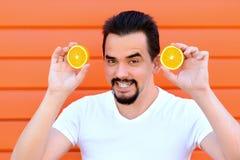 Portret die van een knappe volwassen mens met brede netelige glimlach en baard twee sappige citrusvruchten houden Het concept van royalty-vrije stock fotografie
