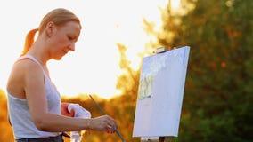 Portret die van een meisje met wit haar in een witte t-shirt, een landschap op canvas in zonsondergang in de zon afschilderen die stock videobeelden
