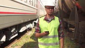 Portret die van een mens in glazenarbeider in een helm en eenvormig, op het station met de telefoon lopen stock videobeelden
